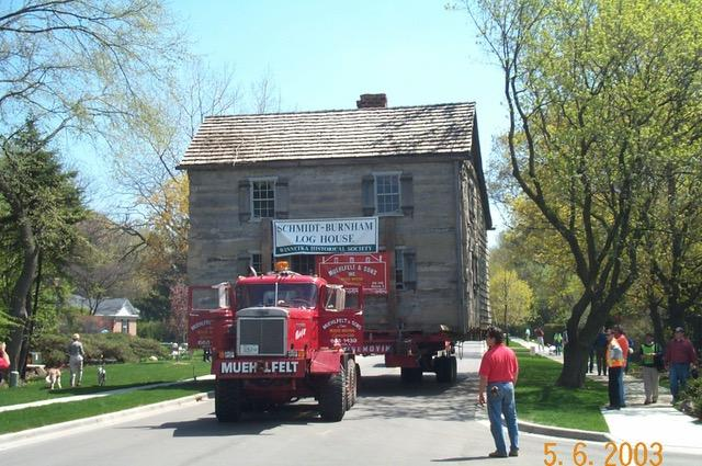May 6: 2003: The Schmidt-Burnham Log House travels west on Tower Road, clocking in at about 3mph. While the news media helicoptered overhead, a couple of hundred kids and adults lined the road to marvel at the spectacle.